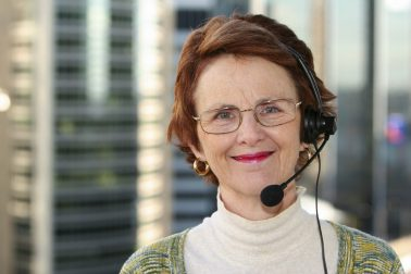 Smiling mature woman with headset. Office buildings in the background.