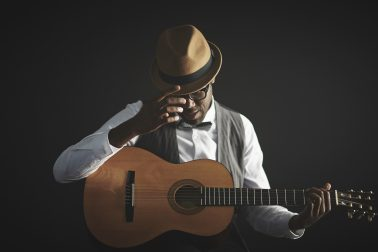 Elegant young man in smart clothes and hat holding guitar