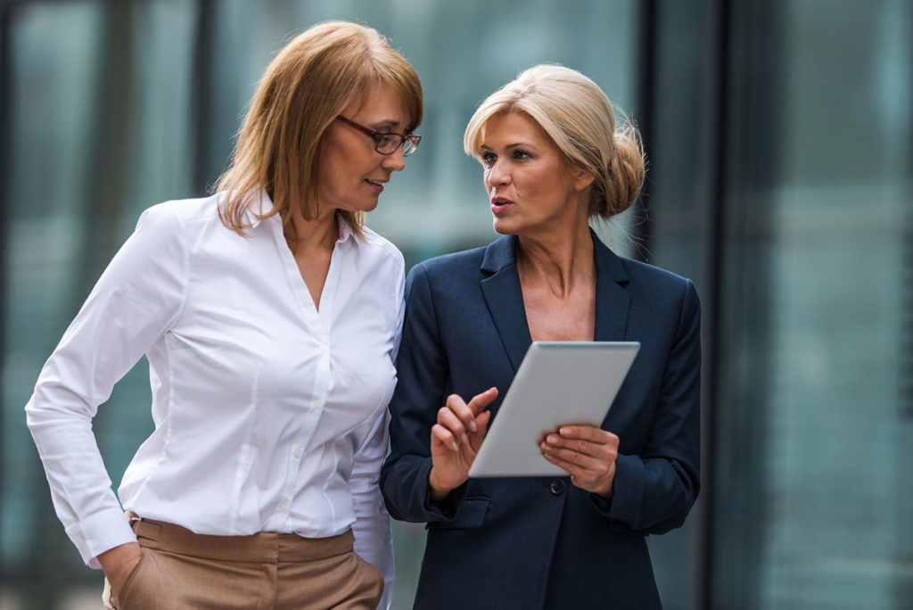 two business women talking, holding paper